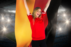 Cheering football fan in red holding germany flag Royalty Free Stock Photography