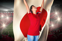 Cheering football fan in red holding japan flag Royalty Free Stock Images