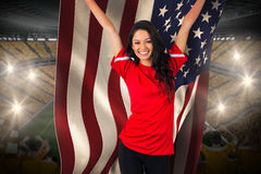 Cheering football fan in red holding usa flag. Against vast football stadium with fans in yellow Stock Photo