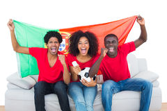 Cheering football fans in red sitting on couch with portugal flag Royalty Free Stock Photos