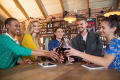 Cheering friends toasting beer bottles and wine glasses. On table in pub Stock Photos