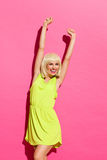 Cheering girl. Smiling blond girl in lime dress standing with arms raised. Three quarter length studio shot on pink background Royalty Free Stock Photography