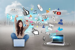 Cheering girl using laptop with app icons Stock Photo