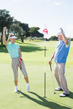 Cheering golfing couple on the eighteenth hole Stock Image
