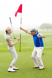 Cheering golfing couple. On a foggy day at the golf course Royalty Free Stock Images