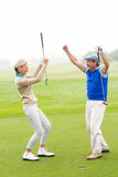 Cheering golfing couple. On a foggy day at the golf course Stock Images