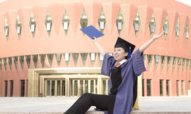 A cheering graduate. An asian miss graduate is sitting and cheering in campus Royalty Free Stock Photo