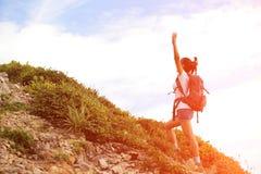 Cheering happy asian woman hiker at mountain peak Stock Photo
