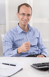 Cheering and happy businessman sitting in his office making winn Royalty Free Stock Photos