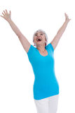 Cheering happy older woman isolated in a blue shirt. royalty free stock images