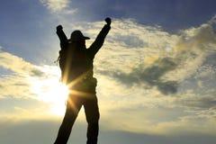 Cheering hiker open arms on sunset mountain peak Royalty Free Stock Photos