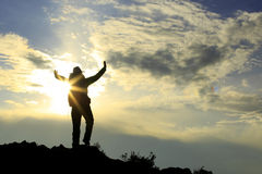cheering hiker open arms on sunset mountain peak Stock Images