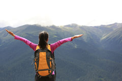 Cheering hiking woman enjoy the beautiful view at mountain peak Stock Photos