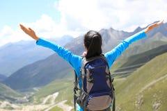 Cheering hiking woman enjoy the beautiful view at mountain peak Stock Photo