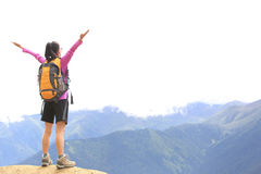 Cheering hiking woman open arms on mountain peak Stock Images