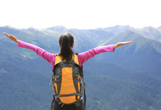 Cheering hiking woman open arms on mountain peak Royalty Free Stock Photography