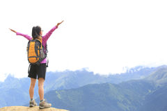 Cheering hiking woman open arms on mountain peak Stock Photo
