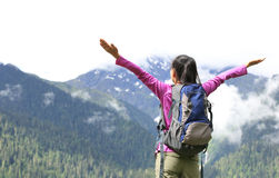 Cheering hiking woman open arms on mountain peak Stock Photos