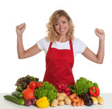 Cheering housewife with red apron and fresh vegetables Royalty Free Stock Images
