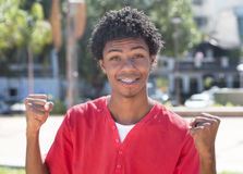 Cheering latin american guy with dental braces. Outdoor in the city in the summer stock image