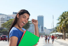 Cheering latin student with long dark hair in the city Royalty Free Stock Photography