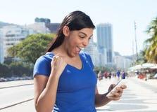 Cheering latin woman receiving good news on cellphone Stock Photos