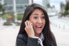 Cheering latin woman talking at phone in the city Royalty Free Stock Images