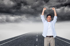 Cheering male with arms up. Composite image of cheering male with arms up Royalty Free Stock Photos