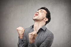 Cheering man. Exulting man with fits up and screaming Stock Images