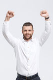 Cheering man with raised arms. Celebration of achievement. Portrait of handsome man with beard holding his fists raised against isolated white background Royalty Free Stock Photography