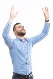 Cheering man with raised arms. Praying to you. Handsome middle-aged man with beard raising his arms in air against isolated background Royalty Free Stock Images
