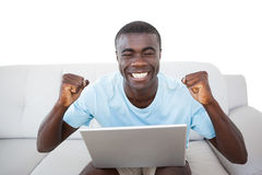 Cheering man sitting on couch using laptop Royalty Free Stock Photos