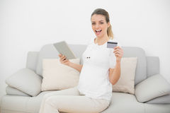 Cheering pregnant woman showing her tablet and credit card looking at camera Royalty Free Stock Photos