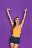 Cheering Girl Looking Up And Rising Arms. Happy young woman in orange shirt and jeans shorts posing with arms outstretched and looking up. Three quarter length royalty free stock photos