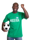 Cheering soccer fan from Nigeria with ball Stock Photo