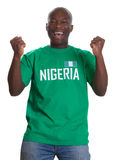 Cheering sports fan from Nigeria. Is happy about his national team on an isolated white background royalty free stock photography