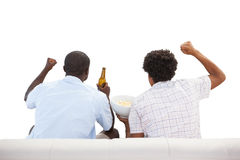 Cheering sports fans sitting on the couch with beers Stock Images