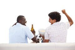 Cheering sports fans sitting on the couch with beers Royalty Free Stock Photos