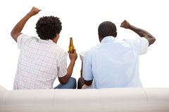 Cheering sports fans sitting on the couch with beers Royalty Free Stock Photography