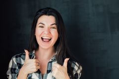 Cheering supportive emotional lady portrait. Closeup portrait of brunette girl on dark background. Supportive emotional lady cheering with thumbs up. Happy royalty free stock image