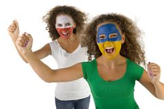 Cheering twins. Female screaming fans with painted Slovakian and Polish flags on faces. They're looking at camera. Focus on first person. They're on white Royalty Free Stock Photography