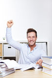 Cheering university student. With clenched fist at desk with many books Royalty Free Stock Image