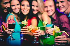 Cheering up. Glasses with cocktails held by happy friends at party stock image