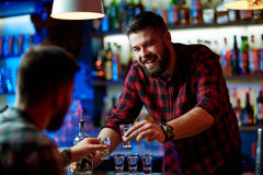 Cheering up. Happy barman cheering up with guy Stock Images