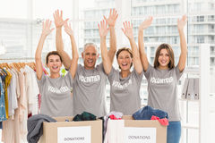 Cheering volunteers holding arms up. Portrait of cheering volunteers holding arms up in the office Royalty Free Stock Images