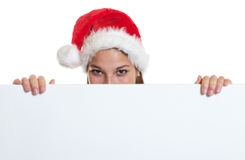 Cheering woman with christmas hat behind a signboard Royalty Free Stock Photo