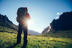 Woman hiker with backpack hiking on high altitude mountain. Cheering woman hiker with backpack hiking on high altitude mountain royalty free stock photos