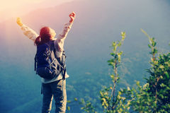 Cheering woman hiker open arms at mountain peak Royalty Free Stock Photography