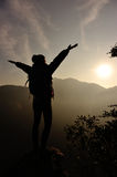 Cheering woman hiker open arms at mountain peak Stock Image