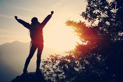 Cheering woman hiker open arms at mountain peak Royalty Free Stock Photos